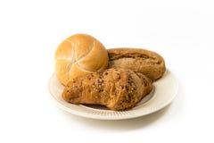 Tre rullar av bröd på en off-whiteaste platta Arkivfoto