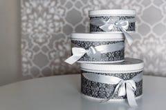 Tre runda berömgåvaaskar med silverbandet bugar på den vita tabellen Bunt av gåvor i lyxig inre Royaltyfria Foton