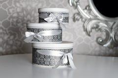 Tre runda berömgåvaaskar med silverbandet bugar på den vita tabellen Bunt av gåvor i lyxig inre Royaltyfri Bild