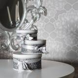 Tre runda berömgåvaaskar med silverbandet bugar på den vita tabellen Bunt av gåvor i lyxig inre Fotografering för Bildbyråer