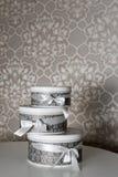 Tre runda berömgåvaaskar med silverbandet bugar på den vita tabellen Bunt av gåvor i lyxig inre Royaltyfria Bilder