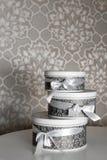 Tre runda berömgåvaaskar med silverbandet bugar på den vita tabellen Bunt av gåvor i lyxig inre Royaltyfri Foto