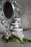 Tre runda berömgåvaaskar med silverbandpilbågar på den vita tabellen och buketten av orkidér Staplade gåvor in Royaltyfria Bilder