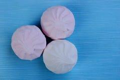 Tre runda vita rosa marshmallower på en blå tabell Arkivbild