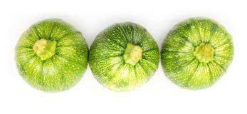 Tre runda zucchinier i rad Arkivbild