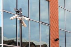 Tre säkerhetskameror på framdel av glass byggnad Fotografering för Bildbyråer
