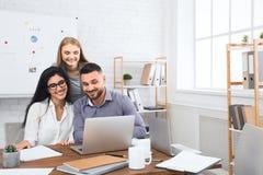 Tre säkra affärspersoner som diskuterar nytt projekt arkivfoto