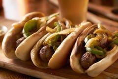 Tre salsiccie del bratwurst con le cipolle arrostite ed i peperoni dolci fotografia stock libera da diritti