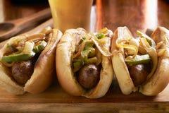 Tre salsiccie del bratwurst con le cipolle arrostite ed i peperoni dolci immagini stock libere da diritti