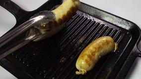 Tre salsiccie sono fritte in una padella La mano del cuoco con il forcipe li impernia sulla griglia Movimento lento video d archivio