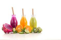 Tre sapori del succo di frutta in bottiglie con una paglia islolated su fondo bianco fotografia stock