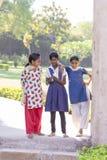 Tre scolare indiane della ragazza stanno nell'iarda in villaggio Mandu, India fotografie stock libere da diritti