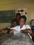Tre scolari primari facendo uso della compressa in aula Fotografia Stock