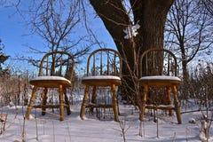 Tre sedie di legno lasciate nella neve Immagini Stock