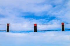 Tre semafori rossi appendono sopra la strada contro il cielo blu Segnale di proibizione Fotografia Stock