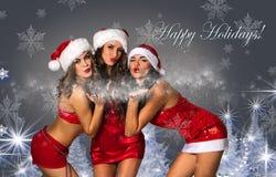 Tre sexiga jultomten hjälpredor som blåser snö Arkivfoton
