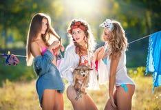 Tre sexiga kvinnor med provokativa dräkter som sätter kläder för att torka i sol Sinnliga unga kvinnlig som skrattar sätta ut tva Fotografering för Bildbyråer