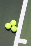 Tre sfere di tennis sulla riga di servizio Immagine Stock Libera da Diritti