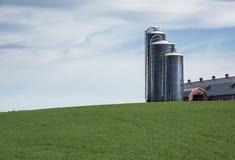 Tre silos di grano su Hillside erboso Immagini Stock