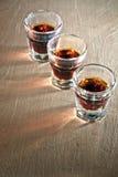 Tre sköt exponeringsglas full av mörk kulör alkohol Arkivfoton
