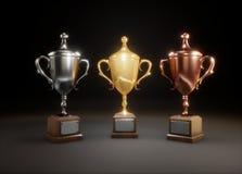 Tre skinande koppvinnare på svart bakgrund Guld, silver och br Royaltyfri Fotografi