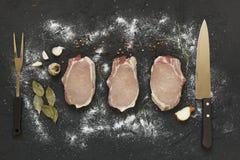 Tre skivor, rått kött som är rått, T-ben biff, nya örter som ÄR SALTA, vitlök, lök, peppar på en mörk stenbakgrund, bästa sikt Royaltyfria Foton