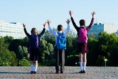 Tre skolbarn som går vänskapligt i parkera, och lyfter deras händer uppåt royaltyfri foto