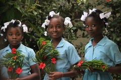 Tre skolflickor rymmer välkomnande kransar för missionärer i lantliga Robillard, Haiti Arkivfoto