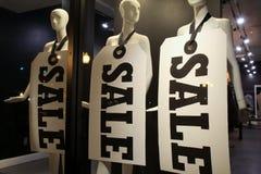 Tre skyltdockor med stora SALE undertecknar runt om deras halsar Royaltyfria Foton