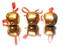 Tre slädeklockor med röda bandpilbågar Royaltyfri Foto