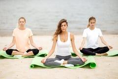 Tre slanka unga flickor sitter i en yoga poserar med bokslut?gon p? mats p? den sandiga stranden bredvid floden p? en varm dag royaltyfri fotografi