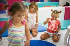 Tre små flickor i lekplats royaltyfri bild
