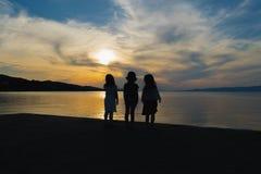 Tre små flickor som håller ögonen på solnedgången mot en dramatisk himmel Arkivbilder