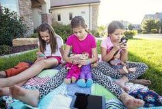 Tre små flickor som spelar på deras smarta telefoner, i stället för samtal fotografering för bildbyråer