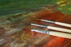 Tre smutsiga borstar på abstrakt målarfärg Arkivbilder
