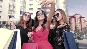 Tre sofistikerade kvinnliga vänner som har gyckel tillsammans, når att ha tyckt om en shoppingtur stock video