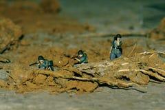 Tre soldati stanno tendendo un'imboscata in campo di battaglia immagini stock