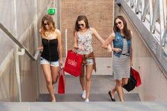 Tre som den härliga kvinnan går upp trappan, dem, går att shoppa Royaltyfri Foto