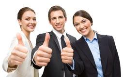 Tre som tummar upp affärsfolk Arkivfoton