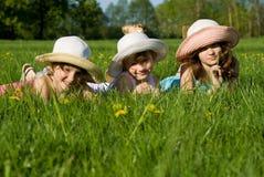 Tre sorelle che si trovano sull'erba Fotografie Stock Libere da Diritti