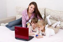Tre sorelle fanno gli acquisti via il Internet Immagini Stock Libere da Diritti