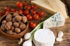 Tre sorter av ost och flera sorter av grönsaken Arkivbilder