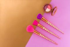 Tre spazzole ed ombretti su una doppia porpora - fondo dell'rame-oro fotografia stock