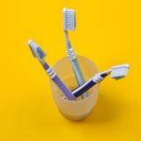 Tre spazzolini da denti in un vetro Immagini Stock