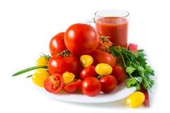 Tre specie dei pomodori, del giallo rosso e della ciliegia su un piatto bianco Isolato su priorità bassa bianca fotografie stock libere da diritti