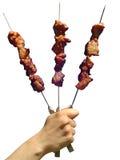 Tre spiedi dei kebabs dello shish in una mano dell'uomo Immagine Stock Libera da Diritti