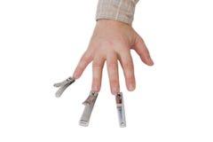 Tre spikar nagelsax mitt emot fingrarna av en manlig hand Arkivfoto