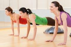 Tre sportiga kvinnor som gör övning på boll Royaltyfri Foto