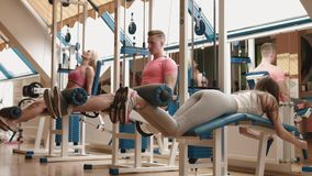 Tre sportive vänner på idrottshallen Den muskulösa mannen och magra kvinnor utarbetar tillsammans 4K stock video