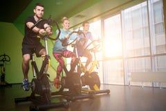 Tre sportsmens sulle bici di esercizio Immagini Stock